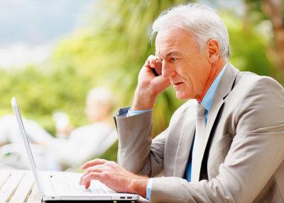 old man searching on laptop